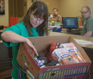Judy Oerly gathers food she will be taking home from the Central Pantry in Columbia, Mo., on 10/4/13.